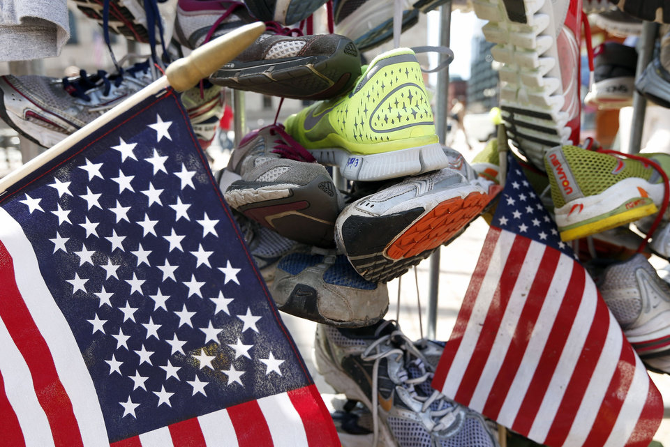 Photo - Running shoes hang from a barrier at a makeshift memorial in Copley Square on Boylston Street in Boston, Wednesday, April 24, 2013. Traffic was allowed to flow all the way down Boylston Street on Wednesday morning for the first time since two explosions on April 15. (AP Photo/Michael Dwyer)
