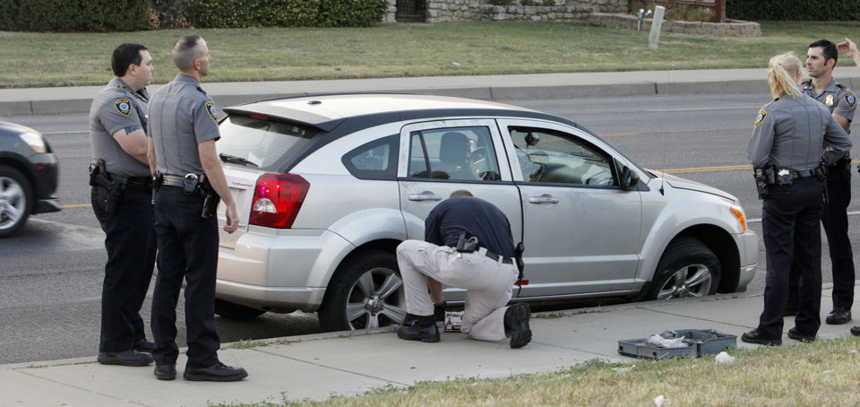 Photo - Oklahoma City police watch as a Norman Police  Department investigator processes a car.  Photo by Paul B. Southerland, The Oklahoman
