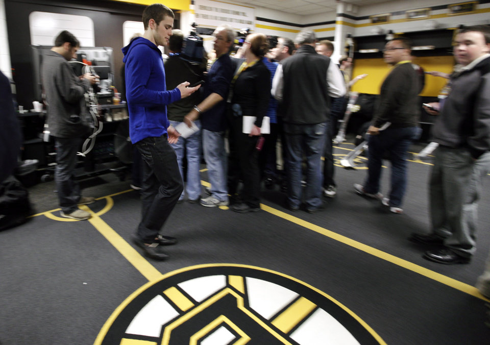 Photo -   Boston Bruins center Tyler Seguin checks his cellphone as he walks through the locker room at TD Garden in Boston, Friday, April 27, 2012, where media gathered to report about their loss to the Washington Capitals in Game 7 and the Bruins' elimination from the Stanley Cup hockey playoffs. (AP Photo/Elise Amendola)