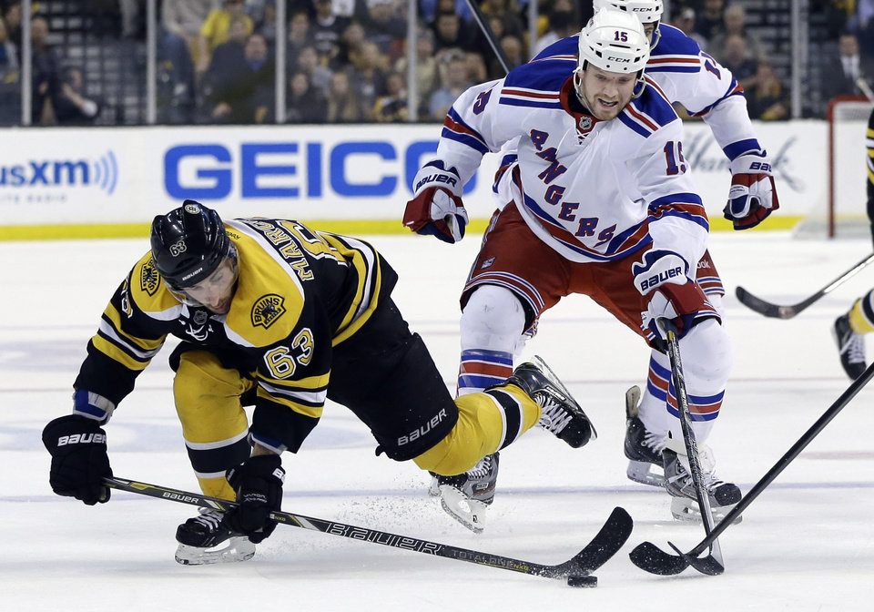 Photo - Boston Bruins left wing Brad Marchand (63) gets to the puck ahead of New York Rangers right wing Derek Dorsett (15) during the second period in Game 2 of the NHL Eastern Conference semifinal hockey playoff series in Boston, Sunday, May 19, 2013. (AP Photo/Elise Amendola)
