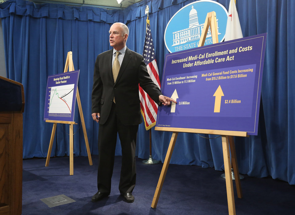 Photo - Gov. Jerry Brown  gestures to a board showing the increase in the state's health care costs as he unveils his revised 2014-15 state budget at the Capitol in  Sacramento, Calif., Tuesday, May 13, 2014.  The revised budget projects $107.7 billion in spending from the general fund, that's nearly $1 billion more than the budget Brown proposed in January.(AP Photo)