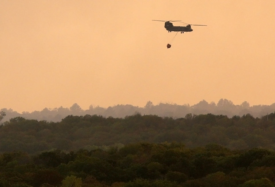 A Chinook helicopter flies to pick up more water at sunset as a wildfire burns through Cleveland County near Norman, Okla., Friday, Aug. 3, 2012. Photo by Nate Billings, The Oklahoman