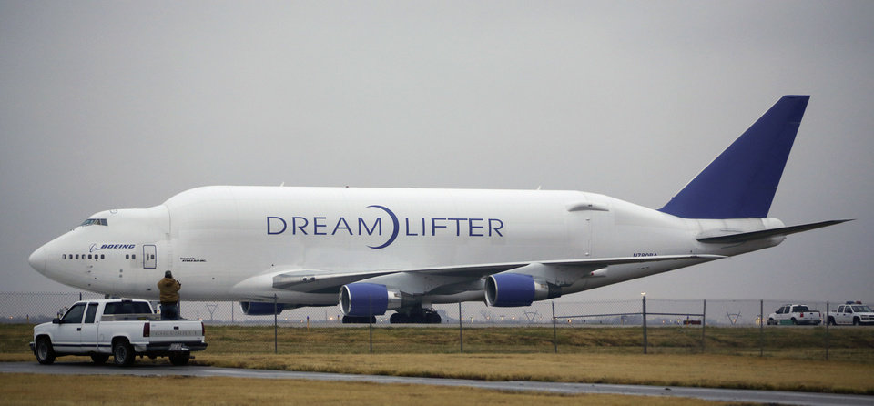 Photo - A man takes a photo of the Boeing 747 LCF Dreamlifter from the back of his truck, Thursday, Nov. 21, 2013, after the aircraft accidentally landed at Col. James Jabara Airport in Wichita, Kan. Wednesday night. Boeing says the Dreamlifter, a 747 jumbo jet used to haul parts for construction of its new 787 Dreamliner, landed safely at Jabara, about eight miles from McConnell Air Force Base in Wichita where it was supposed to land. (AP Photo/Wichita Eagle, Jaime Green) LOCAL TV OUT; MAGS OUT; LOCAL RADIO OUT; LOCAL INTERNET OUT