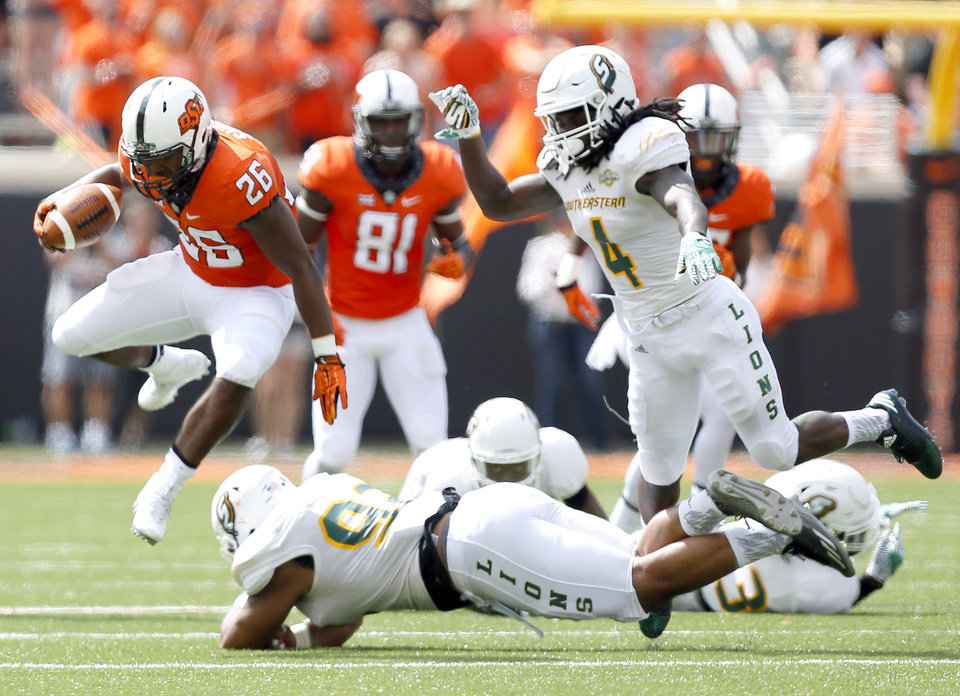 Photo - Oklahoma State's Barry J. Sanders (26) leaps over Southeastern Louisiana's Miki Fangatua (92) as Jeff Williams (4) looks on during the college football game between the Oklahoma State Cowboys (OSU) and the Southeastern Louisiana Lions at Boone Pickens Stadium in Stillwater, Okla., Saturday, Sept. 12, 2015. Photo by Sarah Phipps, The Oklahoman