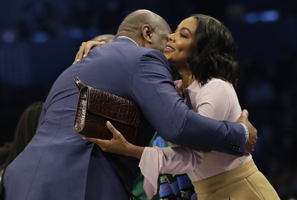 Photo - Actress Gabrielle Union embraces former NBA player Magic Johnson during the second half of an NBA All-Star basketball game, Sunday, Feb. 17, 2019, in Charlotte, N.C. (AP Photo/Chuck Burton)