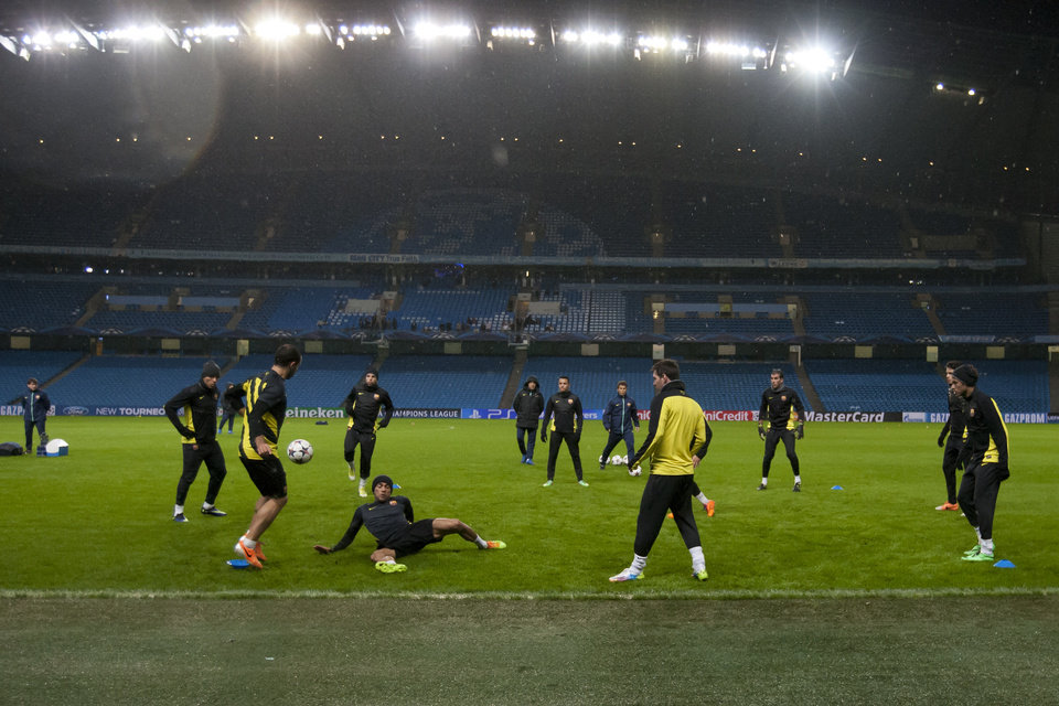 Photo - Barcelona's players train in the rain at Manchester City's Etihad Stadium, Manchester, England, Monday Feb. 17, 2014. Barcelona will play Manchester City on Tuesday in a Champions League first knock out round soccer match. (AP Photo/Jon Super)