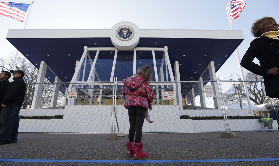 Photo - Evalina Lentini, of Ohio, looks at the Presidential viewing stand near the White House on Pennsylvania Avenue, Sunday, Jan. 20, 2013, in Washington. Thousands are expected to march during the 57th Presidential Inauguration parade after the ceremonial swearing-in of President Barack Obama on Monday. (AP Photo/Steve Helber)