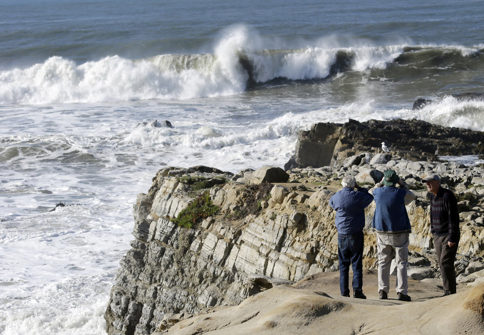 Photo - Visitors watch waves crash on a cliff in Pescadero, Calif., Thursday, Dec. 13, 2012. The National Weather Service says so-called King Tides — caused by a rather unique combination of how the sun, the moon and the earth align — will bring the highest tides of the year on Thursday, Friday and Saturday mornings. Along with the high tides, forecasters say a building swell will bring large breaking waves to area beaches. (AP Photo/Marcio Jose Sanchez)