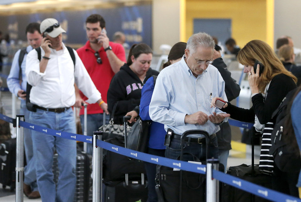Photo - Passengers at O'Hare International Airport wait in a United Airlines ticketing line Tuesday, May 13, 2014, in Chicago. Smoke in a regional radar facility forced a halt to all incoming and outgoing flights at both of Chicago's airports. The Federal Aviation Administration says all its personnel were evacuated from the Chicago Terminal Radar Approach Control, or TRACON, facility in suburban Elgin at around 11:30 a.m. Tuesday.(AP Photo/Charles Rex Arbogast)
