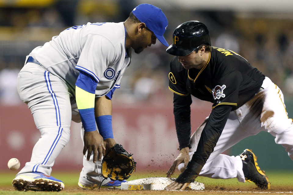 Photo - The ball gets past Toronto Blue Jays third baseman Juan Francisco as Pittsburgh Pirates' Neil Walker, right, takes third on a wild pitch in the fifth inning of the baseball game on Friday, May 2, 2014, in Pittsburgh. (AP Photo/Keith Srakocic)