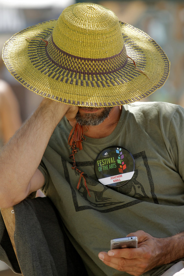 Photo - Artist Joachim Knill checks his phone during opening day of the Festival of the Arts in downtown Oklahoma City TUesday, April 24, 2012. Photo by Doug Hoke, The Oklahoman