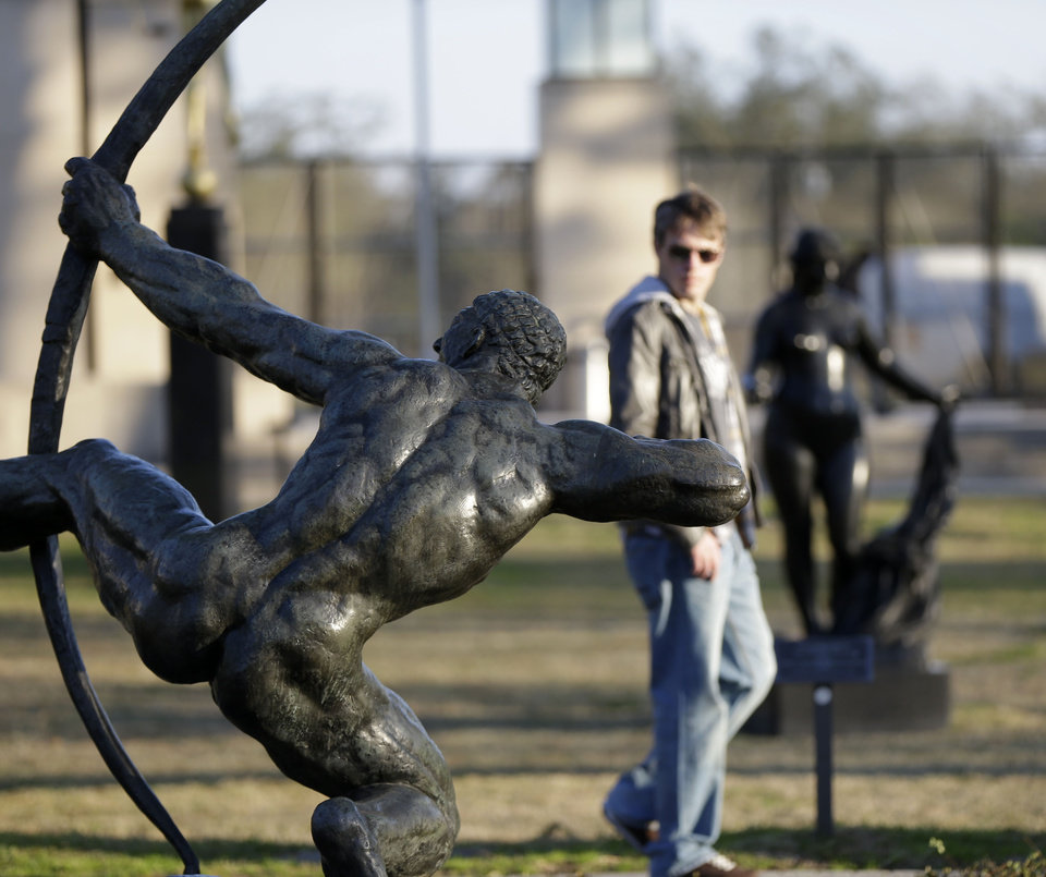 Photo - People walk through the Sydney Walda Besthoff Sculpture Garden in City Park in New Orleans, Tuesday, Jan. 15, 2013. The New Orleans Museum of Art is located in the park, and while there's a fee to enter the museum, just beyond the museum are dozens of art objects you can see for free in the Sydney and Walda Besthoff Sculpture Garden. The sculptures, valued at more than $25 million, can be viewed in a relaxing setting that includes meandering footpaths, pedestrian bridges and reflecting lagoons.  (AP Photo/Gerald Herbert)