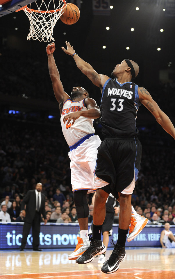 Minnesota Timberwolves' Dante Cunningham (33) blocks the shot of New York Knicks' Raymond Felton (2) in the first half of an NBA basketball game on Sunday, Dec., 23, 2012, at Madison Square Garden in New York. (AP Photo/Kathy Kmonicek)