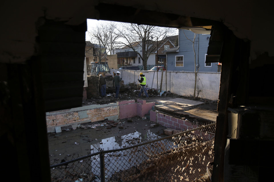Men clean-up debris around the basement of a recently demolished home that was damaged by Superstorm Sandy in Staten Island, New York, Thursday, Jan. 10, 2013.  (AP Photo/Seth Wenig)