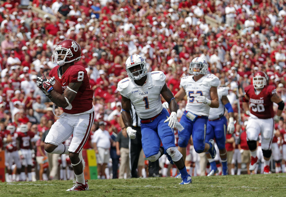 Photo - Oklahoma's Jalen Saunders (8) makes a touchdown catch in front of Tulsa 's Michael Mudoh (1) during the college football game between the University of Oklahoma Sooners (OU) and the University of Tulsa Hurricanes (TU) at the Gaylord-Family Oklahoma Memorial Stadium on Saturday, Sept. 14, 2013 in Norman, Okla.  Photo by Chris Landsberger, The Oklahoman