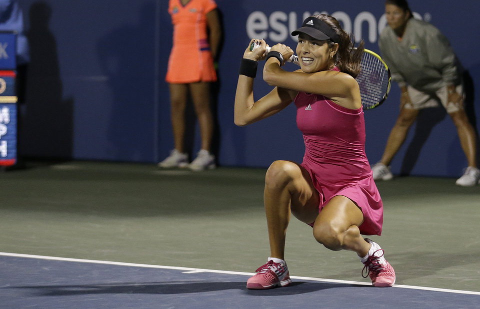 Photo - Ana Ivanovic, from Serbia, returns the ball to Serena Williams during the third set of their match in the Bank of the West Classic tennis tournament in Stanford, Calif., Friday, Aug. 1, 2014. Williams won 2-6, 6-3, 7-5. (AP Photo/Jeff Chiu)