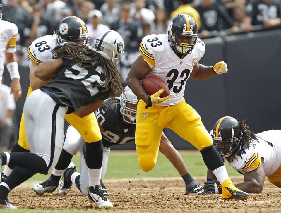 Photo -   Pittsburgh Steelers running back Isaac Redman carries the ball past Oakland Raiders outside linebacker Philip Wheeler (52) as tight end Heath Miller (83) blocks during the first quarter of an NFL football game in Oakland, Calif., Sunday, Sept. 23, 2012. (AP Photo/Tony Avelar)