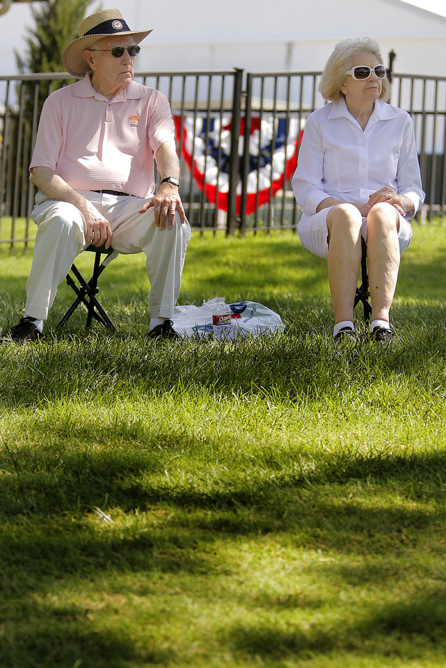 Photo - Oak Tree residents Gene and Dortha Geren find a spot in the shade near the fourth hole green as they watch the practice rounds for the U.S. Senior Open golf tournament at Oak Tree National in Edmond, Okla. on Monday, July 7, 2014. Photo by Chris Landsberger, The Oklahoman