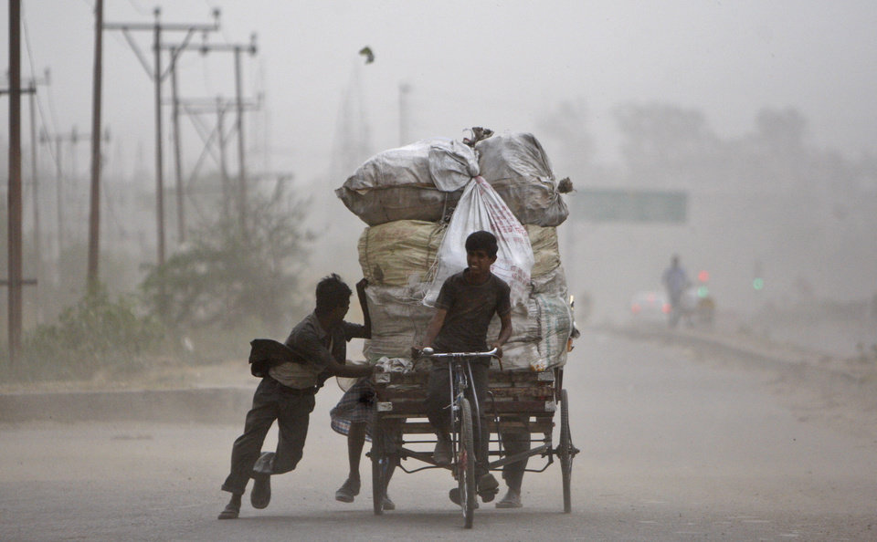 A ragpicker pedals a loaded cart as others help by pushing it on a road during a dust storm in Jammu, India, Saturday, May 11,2013. (AP Photo/Channi Anand)