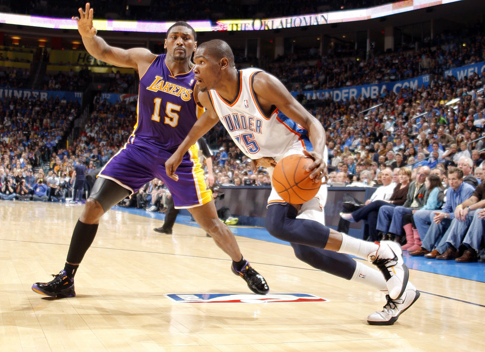 Photo - L.A. LAKERS: Oklahoma City's Kevin Durant (35) drives past Lakers' Ron Artest (15) during the NBA basketball game between the Oklahoma City Thunder and the Los Angeles Lakers, Sunday, Feb. 27, 2011, at the Oklahoma City Arena. Photo by Sarah Phipps, The Oklahoman  ORG XMIT: KOD