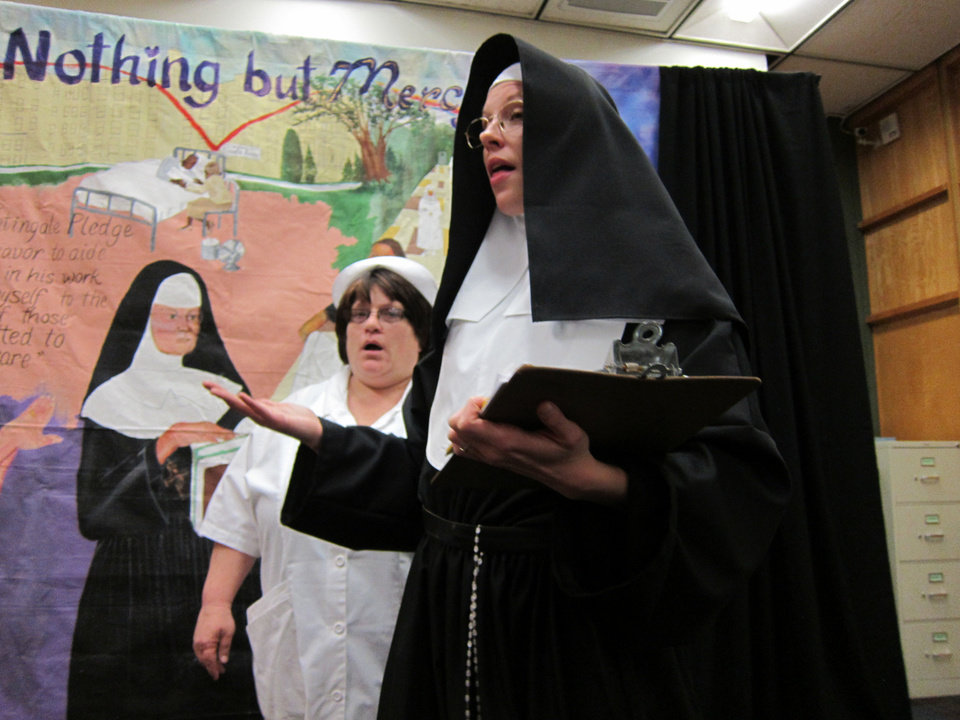 Photo - Nurse Martha, portrayed by Sandra Oliver, listens to Sister Mary Madeline Feely, portrayed by Amy xxxx, during a performance of the Rhythmically Speaking production of