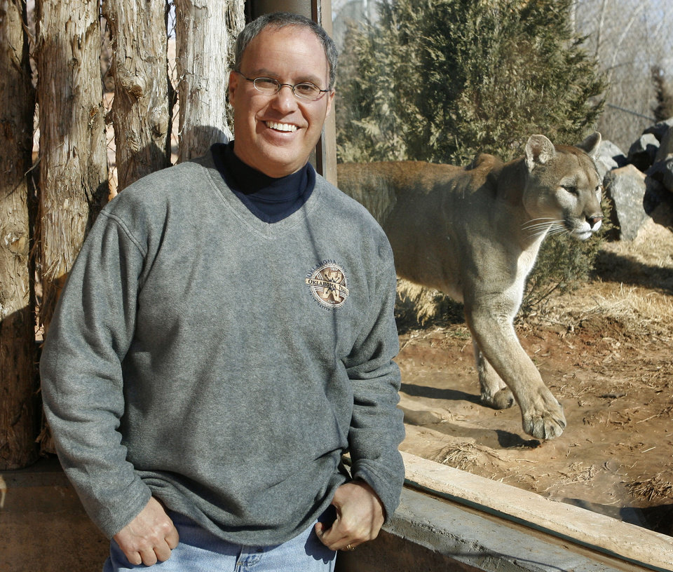 Photo - Oklahoma City Zoo Director Bert Castro stands near a mountain lion at the soon-to-be-opened