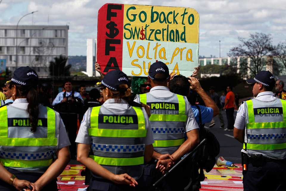 Photo - A protester holds up a sign against FIFA, in front of military police during a protest against the World Cup, in Brasilia, Brazil, Sunday, June 15, 2014. Protesters are unhappy about the money spent on the FIFA 2014 Soccer World Cup, which they believe would have been better spent in improving the country's basic services. (AP Photo/Eraldo Peres)