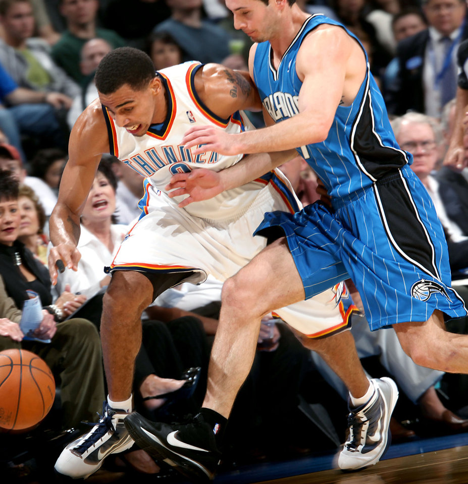 Oklahoma City\'s Thabo Sefolosha and Orlando\'s J.J. Redick chase down a loose ball during the NBA basketball game between the Orlando Magic and the Oklahoma City Thunder at the Ford Center in Oklahoma City, on Sunday, Nov. 8, 2009. By John Clanton, The Oklahoman
