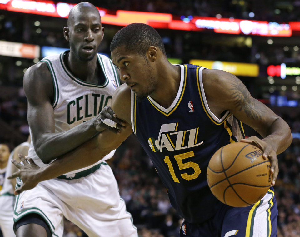 Utah Jazz forward Derrick Favors (15) drives the baseline against Boston Celtics forward Kevin Garnett during the first half of an NBA basketball game in Boston, Wednesday, Nov. 14, 2012. (AP Photo/Elise Amendola)