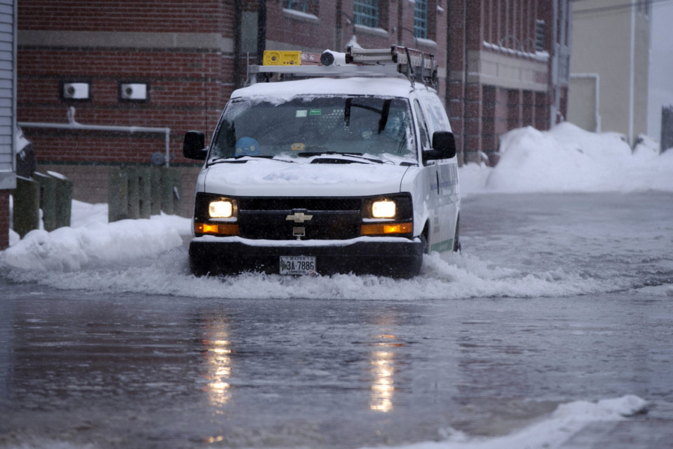 Photo - An electric utilities truck drives over a flooded road along the waterfront during a snowstorm, Thursday, Jan. 2, 2014, in Portland, Maine. Astronomical high tides, strong winds and frigid temperatures are all factors in this latest storm to hit the Northeast. (AP Photo/Robert F. Bukaty)