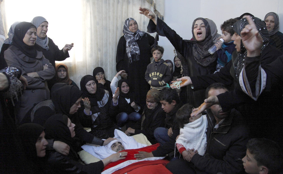 Photo -   Sister of Qais al Omari, 27, and other relatives, gather around his body, prior to his funeral, Friday Nov. 16, 2012, in Kofr Assad village, Jordan, north of the capital, Amman. Al Omari, 27, was shot by Jordanian police, during a demonstration following an announcement of raising fuel prices, including a hike on cooking gas last Tuesday. (AP Photo/Mohammad Hannon)