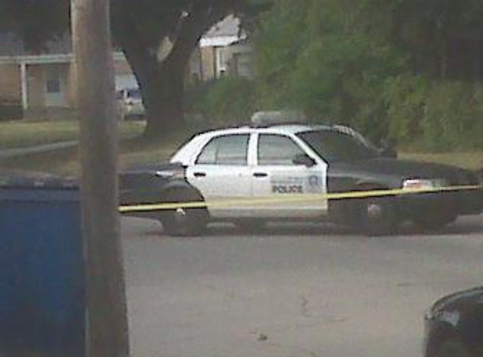 The police car Monday morning in northwest Oklahoma City which was shot at Sunday night. There is a bullet hole on the back passenger side door and damage to passenger side windows. Photo by Robert Medley