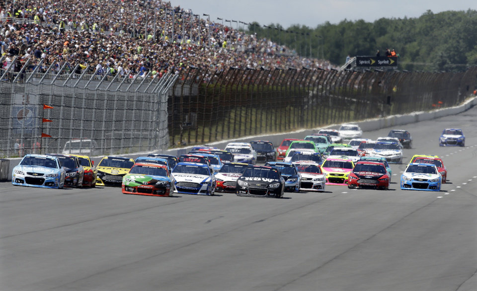 Photo - Driver Jimmie Johnson (48), left, leads from the pole at the start of an NASCAR Sprint Cup Series auto race, Sunday Aug. 4, 2013, at Pocono Raceway in Long Pond, Pa. (AP Photo/Mel Evans)