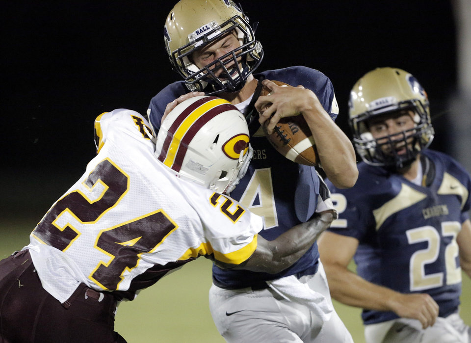 Photo - Heritage Hall's Connor McGinnis (4) is taken down by Clinton's Marquez Simpkins (24) during a high school football game between Heritage Hall and Clinton in Oklahoma City, Friday, Sept. 7, 2012.  Photo by Garett Fisbeck, The Oklahoman