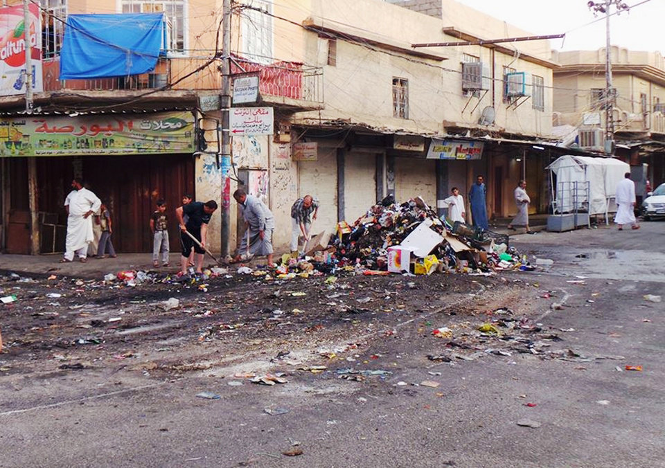 Photo - People clean up a street in the northern city of Mosul, Iraq, Friday, June 13, 2014. Iraqi officials say al-Qaida-inspired militants who this week seized much of the country's Sunni heartland have pushed into an ethnically mixed province northeast of Baghdad, capturing two towns there.(AP Photo)