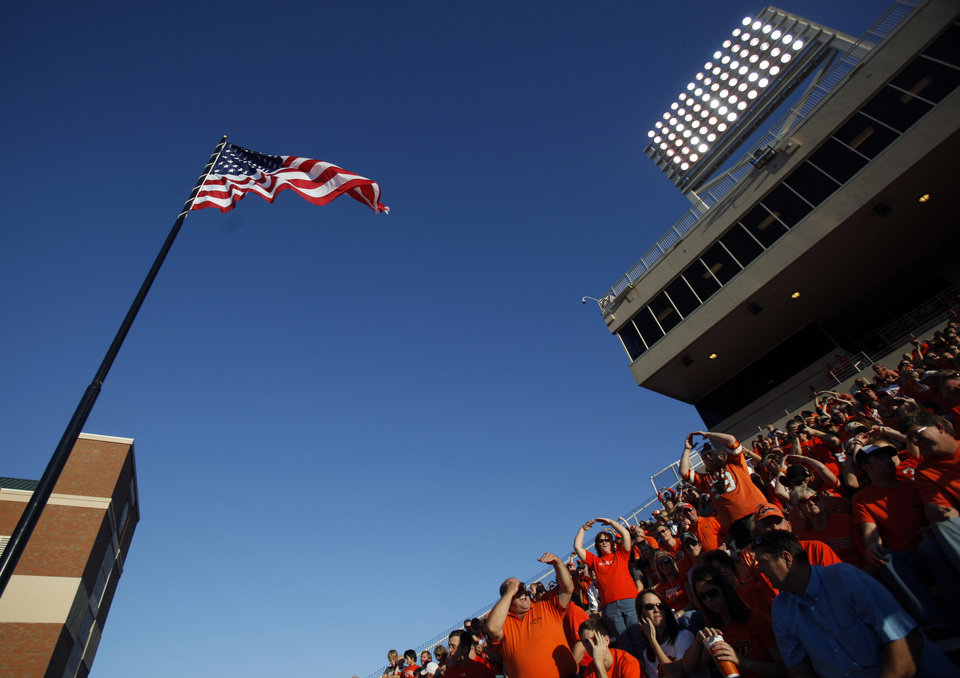 Photo - The flag waves in the wind during Oklahoma State's game vs. Arizona on Thursday. PHOTO BY SARAH PHIPPS, The Oklahoman