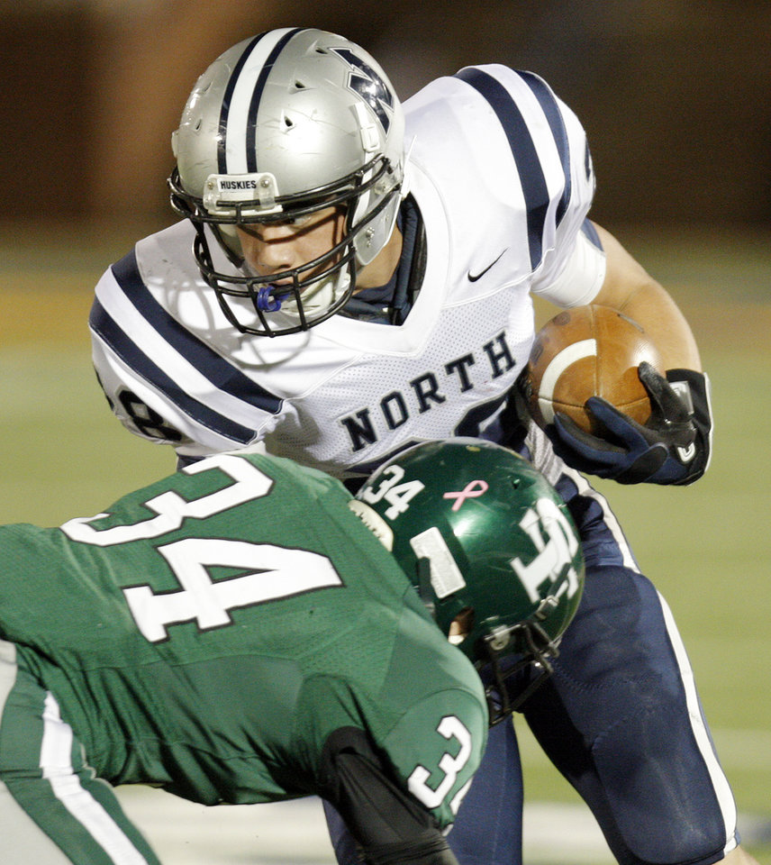 Conner Bays (34) of Edmond Santa Fe tries to stop Troy Davis (28) of Edmond North after a catch during a high school football game between Edmond Santa Fe and Edmond North at Wantland Stadium in Edmond, Okla., Friday, Oct. 28, 2011. Photo by Nate Billings, The Oklahoman