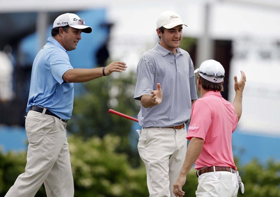 Photo - Scott Gardiner, left, of Australia and Kevin Kisner, right, congratulate Scottie Scheffler, 17, of Highland Park High School in Dallas, after Scheffler sunk a hole-in-one on a 218-yard second hole during the third round of the Byron Nelson Championship golf tournament, Saturday, May 17, 2014, in Irving, Texas. Scheffler is playing in the tournament on a sponsor exemption. (AP Photo/Tony Gutierrez)