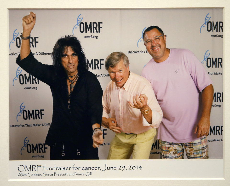 Photo -  A photo of Dr. Stephen Prescott with Alice Cooper and Vince Gill during an OMRF fundraiser hangs in Prescott's office. [PHOTO PROVIDED]