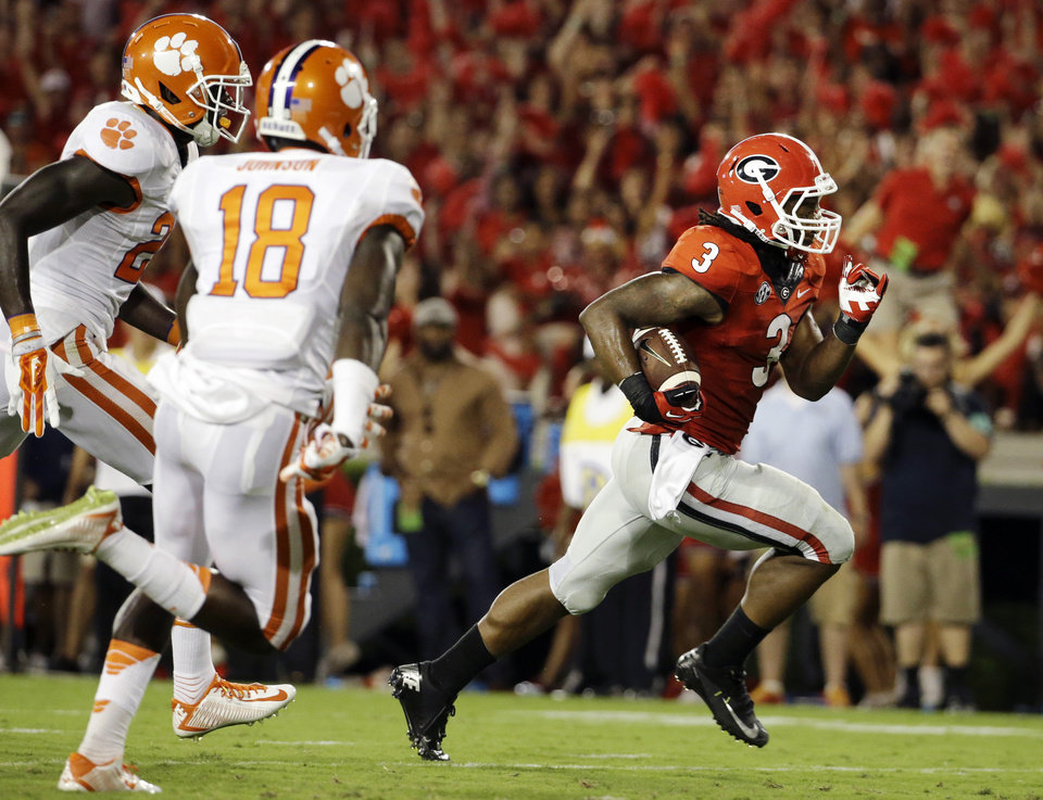 Photo - Georgia's Todd Gurley, right, runs the ball to score a touchdown in the second half of an NCAA college football game against Clemson, Saturday, Aug. 30, 2014, in Athens, Ga. Gurley ran for 198 yards and three touchdowns, returned a kickoff 100 yards for another score, and No. 12 Georgia gained some early style points in the national race with a 45-21 victory over No. 16 Clemson on Saturday night. (AP Photo/David Goldman)