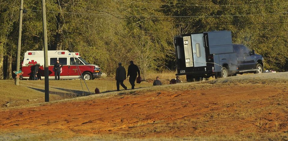 Photo - Police and emergency personnel remain on site at the property of Jimmy Lee Sykes, a suspect accused of holding a 5-year-old boy hostage in an underground bunker on Saturday Feb.  2, 2013 in Midland City, Ala. Negotiators were still trying to persuade Jimmy Lee Dykes to surrender. Police have said they believe the Lee Dykes, a Vietnam-era veteran,  fatally shot a school bus driver Tuesday, and then abducted the boy from the bus and disappeared into the home-made bunker.  (AP Photo/al.com, Joe Songer)