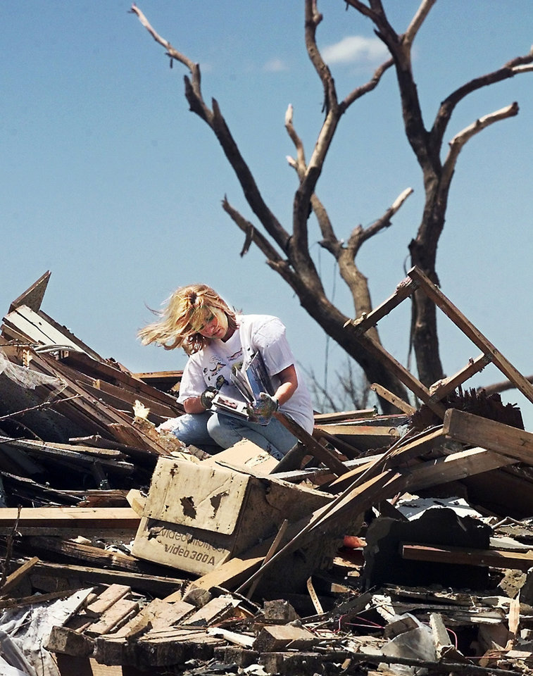 MAY 3, 1999 TORNADO: Tornado victims, damage: Jennifer Squires, 26, looks at a family photo album she found in the rubble of her parents' home in the Del Aire housing addition Wednesday afternoon.  Her parents, Phillip and Karla, Squires were in the house when it was destroyed by Monday night's tornado. They took shelter with their two dogs in a center hallway.  When the tornado hit, another wall was pressed against the interior hallway hall and they were squeezed into a small area.  They were able to escape.  They suffered minor cuts and scrapes;Karla suffered a chipped ankle.