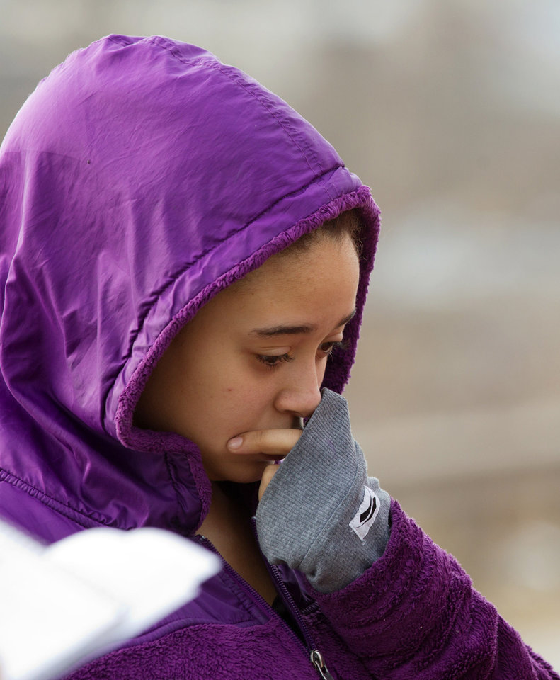 Photo - Mariah Brant cries as she visits the crash site that killed her half-brother, Daylan Ray, early in the morning on Park Ave. in Warren, Ohio on Sunday, March 10, 2013. (AP Photo/Scott R. Galvin)