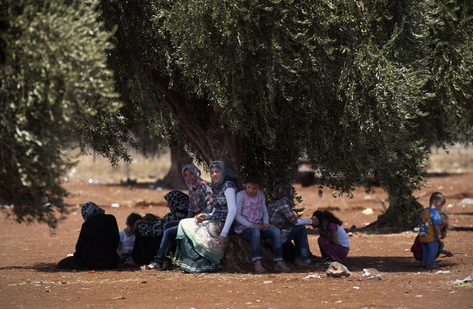 In this Wednesday, Aug. 15, 2012 photo, a Syrian refugee family sit under a tree by the border with Turkey after they left their home, in the town of Azaz on the outskirts of Aleppo, Syria. Thousands of Syrians who have been displaced by the country's civil are struggling to find safe shelter while shelling and airstrikes by government forces continue. (AP Photo/ Khalil Hamra)