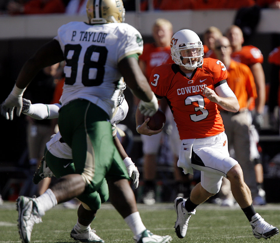 Oklahoma State's Brandon Weeden 93) runs for extra yardage against Baylor's Phil Taylor (98) during the college football game between the Oklahoma State University Cowboys (OSU) and the Baylor University Bears at Boone Pickens Stadium in Stillwater, Okla., Saturday, Nov. 6, 2010. Photo by Chris Landsberger, The Oklahoman