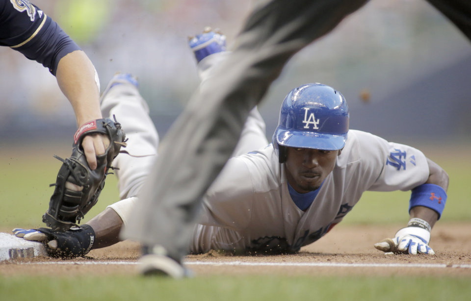 Photo - Los Angeles Dodgers' Dee Gordon, right, is called safe at first base against the Milwaukee Brewers during the sixth inning of a baseball game Saturday, Aug. 9, 2014, in Milwaukee. (AP Photo/Darren Hauck)