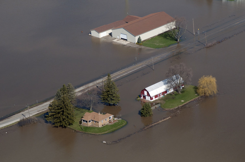 Photo - Buildings in James Township on South Center near the Tittabawassee River are flooded on Monday, April 22, 2013. Area rivers overflowed their banks over the weekend after days of heavy rain saturated the ground. (AP Photo/Jeff Schrier, The Saginaw News)