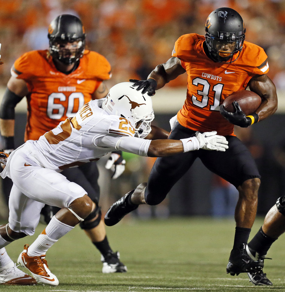 OSU\'s Jeremy Smith (31) tries to rush past UT\'s Josh Turner (25) during a college football game between Oklahoma State University and the University of Texas at Boone Pickens Stadium in Stillwater, Okla., Saturday, Sept. 29, 2012. Photo by Nate Billings, The Oklahoman