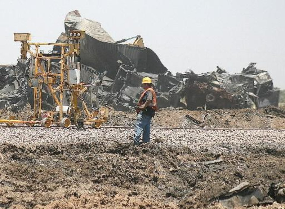Photo - Union Pacific crews work to repair damaged track at the site of a head-on train collision on Monday, June 25, 2012, near Goodwell, Okla. Two Union Pacific locomotives collided on June 24, 2012, killing two crew members and a conductor. (AP Photo/The Guymon Daily Herald, Shawn Yorks)