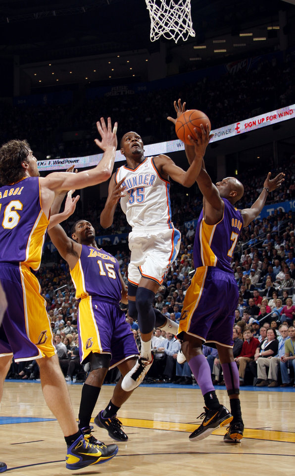 Photo - Oklahoma City's Kevin Durant (35) shoots in between Lakers' Pau Gasol (16), Ron Artest (15) and Lamar Odom (7) during the NBA basketball game between the Oklahoma City Thunder and the Los Angeles Lakers, Sunday, Feb. 27, 2011, at the Oklahoma City Arena.Photo by Sarah Phipps, The Oklahoman